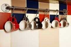Tasses de café colorées sur des crochets photos stock