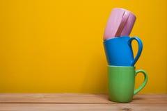 Tasses de café colorées sur la table en bois au-dessus du fond jaune Photographie stock libre de droits