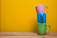 Tasses de café colorées sur la table en bois au-dessus du fond jaune Photos libres de droits