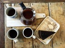 Tasses de café d'égouttement, de pot de café et de morceau de gâteau de chocolat sur la table en bois brune naturelle Photo stock