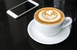 Tasses de café d'art de latte sur la table noire Photographie stock libre de droits