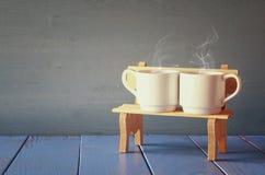 Tasses de café de couples sur le vieux banc Vintage filtré Image libre de droits