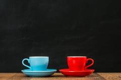Tasses de café en céramique se penchant ensemble sur le bois Image libre de droits