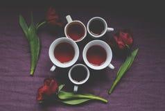 Tasses de café entourées par les tulipes rouges Images stock
