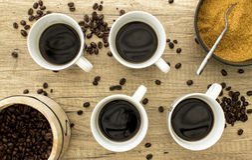 4 tasses de café noir avec les haricots et le sucre sur la surface en bois d'a Image libre de droits