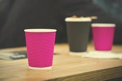 Tasses de café noires et roses de papier de métier en café sur la table en bois Mode de vie, concept de coffeeshop Photographie stock