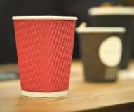 Tasses de café noires et rouges de papier de métier en café sur la table en bois Mode de vie, concept de coffeeshop Photo libre de droits