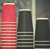 Tasses de café noires et rouges de papier de métier en café sur la table en bois Mode de vie, concept de coffeeshop Images libres de droits