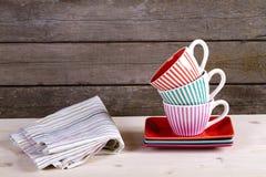 Tasses de café rayées colorées sur l'étagère Images stock