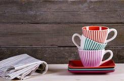 Tasses de café rayées colorées sur l'étagère Photographie stock