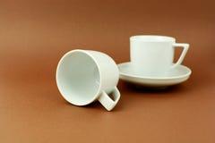 Tasses de café se tenant et s'étendant sur le fond brun Photos stock
