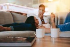 Tasses de café sur la table avec des couples détendant à l'arrière-plan Images stock