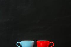 Tasses de café sur le fond noir de mur Photo libre de droits