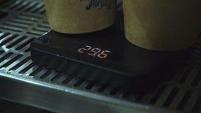 Tasses de café sur les échelles électroniques banque de vidéos