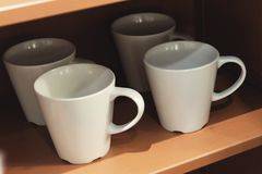 Tasses de café vides accrochant sur les étagères en bois images stock