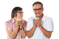 Tasses de café aînées romantiques de fixation de couples Photographie stock