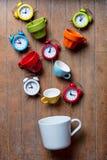 Tasses de couleur avec des réveils Photographie stock