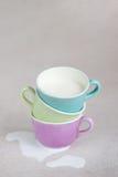 Tasses de couleur avec du lait Image stock