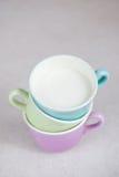 Tasses de couleur avec du lait Photos libres de droits