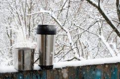 Tasses de fer de boisson chaude sur une terrasse couverte par neige image stock