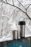 Tasses de fer de boisson chaude sur une terrasse couverte par neige images stock