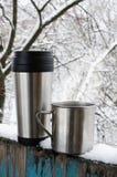 Tasses de fer de boisson chaude sur une terrasse couverte par neige images libres de droits