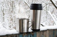 Tasses de fer de boisson chaude sur une terrasse couverte par neige photographie stock libre de droits