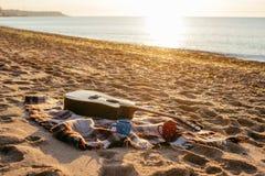 Tasses de guitare et de café sur la plage Photos stock