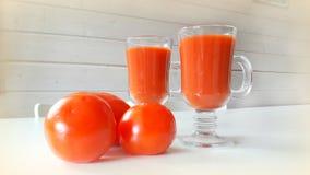 2 tasses de jus de tomates et de quelques tomates sur la table Image libre de droits