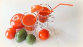 2 tasses de jus de tomates et des certains tomates et avocat sur la table Images stock