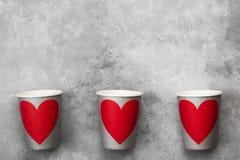 Tasses de papier grises pour des boissons avec le coeur rouge sur un fond clair Images libres de droits