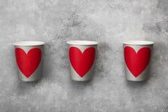 Tasses de papier grises pour des boissons avec le coeur rouge sur un fond clair Photo stock