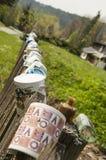 Tasses de porcelaine sur la barrière de jardin Photographie stock