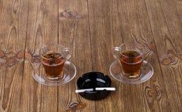 Tasses de thé avec des plats et des cigarettes dans le cendrier Image stock