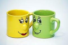 Tasses de thé avec des visages Photos stock