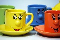Tasses de thé avec des visages Photographie stock