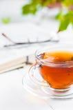 Tasses de thé avec le livre sur la table en bois Image stock