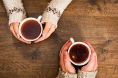 Tasses de thé noir dans les mains des hommes et des femmes Sur un fond en bois Avec l'espace de copie Images libres de droits