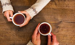 Tasses de thé noir dans les mains des hommes et des femmes Sur un fond en bois Avec l'espace de copie Photos stock