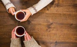 Tasses de thé noir dans les mains des hommes et des femmes Sur un fond en bois Avec l'espace de copie Photos libres de droits