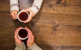Tasses de thé noir dans les mains des hommes et des femmes Sur un fond en bois Avec l'espace de copie Photo libre de droits