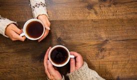 Tasses de thé noir dans les mains des hommes et des femmes Sur un fond en bois Avec l'espace de copie Image libre de droits