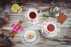 Tasses de thé noir et d'un petit pain Photos stock