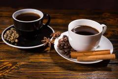 Tasses de thé noires et blanches avec du café et la cannelle Photo libre de droits