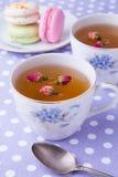 Tasses de tisane avec des macarons sur la serviette de point de polka Photo libre de droits