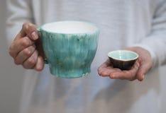 Tasses en céramique sur le fond de couleurs en pastel dans les mains d'une femme photographie stock libre de droits