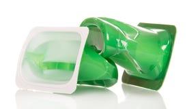 Tasses en plastique écrasées de fin de yaourt sur le blanc Image stock