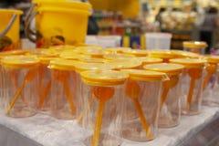 Tasses en plastique avec un doseur dans la fenêtre de boutique image libre de droits