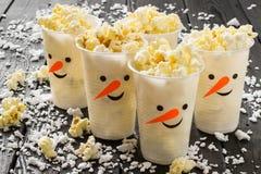 Tasses en plastique sous forme de bonhommes de neige avec le maïs éclaté Image libre de droits