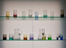 Tasses en verre sur deux étagères en verre Photos stock